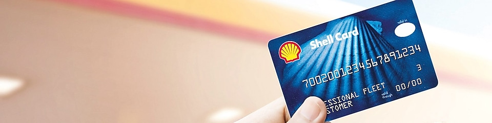 Blue shell fuel card being held between thumb and forefinger