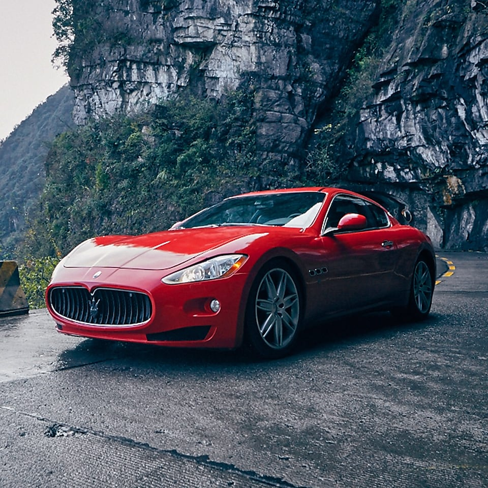 A red Maserati with standard Shell Helix Ultra product proudly sits on a scenic mountain road