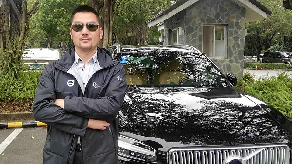 Chen Peng at standing in front of car